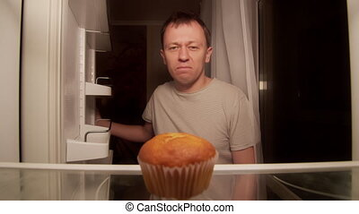 Man opens the refrigerator at night on the shelf is one cupcake, a disgruntled man