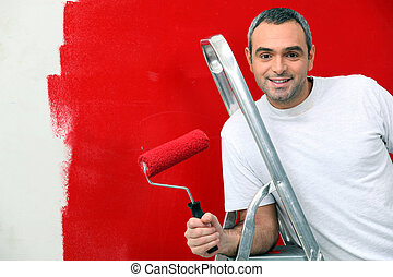 A man painting a wall red