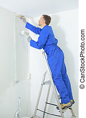 a man painting walls with a brush