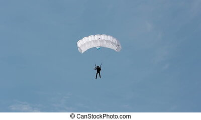 A man parachutes down to the ground. Parachute flight