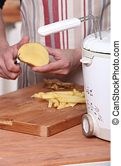 a man peeling potatoes and a fryer