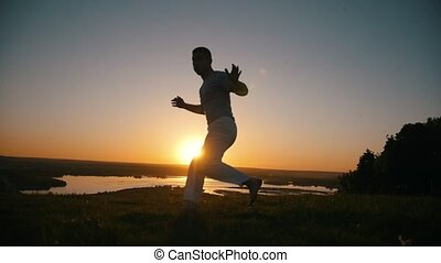 A man performs combat techniques on the background of the setting sun, slow-motion