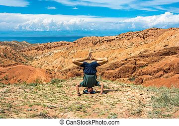 A man performs the asanas in the amazing mountain canyon Tale in summer sunny day, Kyrkyzstan.
