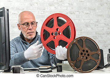 man photographer looking at reel 16mm film