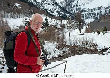 man photographer with camera in the snowy mountain