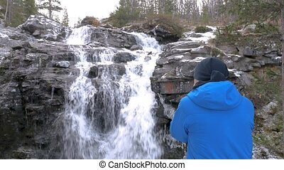 A man photographs a beautiful waterfall in the mountains, on...