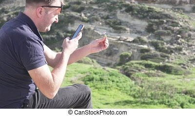 A man photographs a flower on the phone on the background of the sea