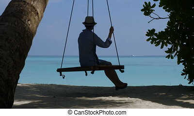 A man photographs a young beautiful girl on a swing. Beautiful beach and ocean.