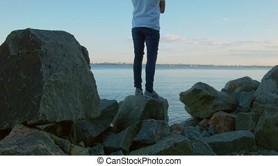 A man photographs the landscape on a smartphone, standing on...