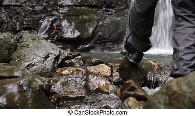 a man picks up water in a bowler from a mountain river. Travel Lifestyle and success concept of vacation in the wild on a mountain background. 4k, slow motion