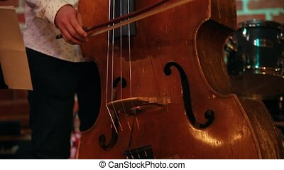 A man playing a double bass in a jazz bar, only his hands...