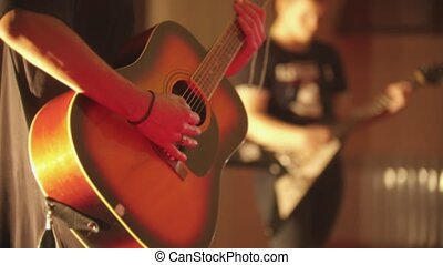 A man playing acoustic guitar - a performance with band in the club