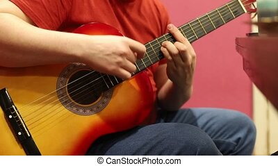 A man playing acoustic guitar indoors