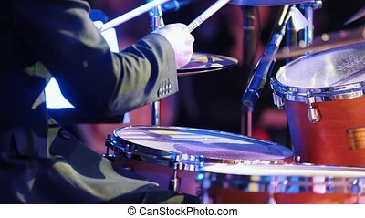 A man playing drums at the jazz concert. Back view. Mid shot