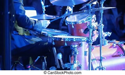 A man playing drums at the jazz concert with colorful...