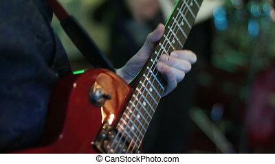 A man playing electric guitar close up