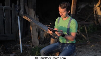 A man playing on a tablet at the sawmill. sunset time