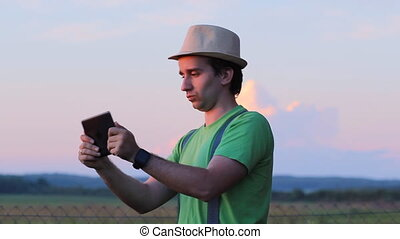 A man playing on a tablet in the game. Against the backdrop of a beautiful sunset sky