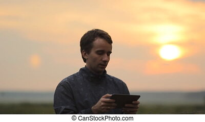 A man playing on a tablet in the game. Beautiful sunset on the background