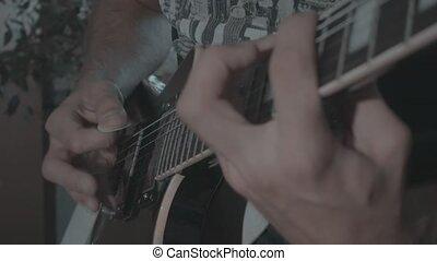 A man plays a black electric guitar