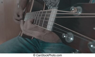 A man plays a solo on an acoustic guitar