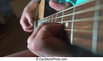 A man plays an acoustic guitar.