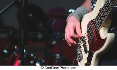 A man plays bass guitar on stage. Hand close-up