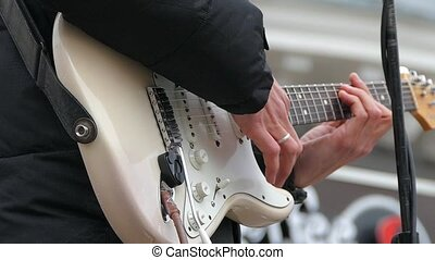 A man plays on electric guitar strings with a white body....
