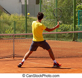 A man plays tennis on the court in the park