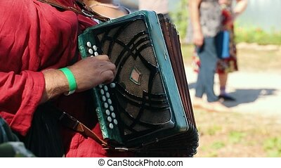 A man plays the accordion and touches his fingers, close up