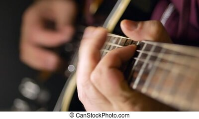 A man plays the guitar. Close-up
