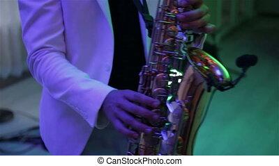 A man plays the saxophone