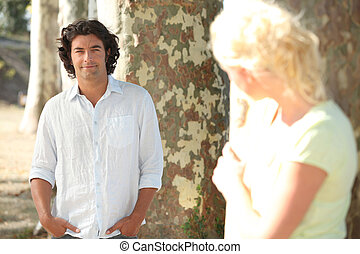a man posing and a blonde woman hidden behind a tree watching him in secret