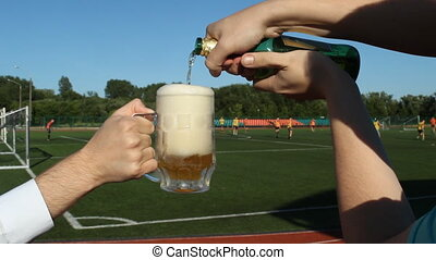 A man pours beer in a glass against the background of a football stadium where they play football, close-up