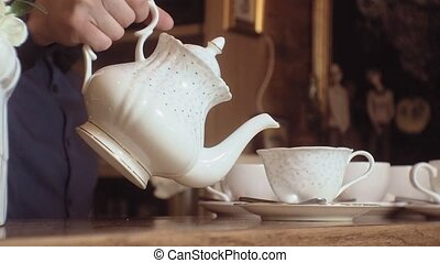 A man pours tea from a kettle into a white cup on a wooden table.
