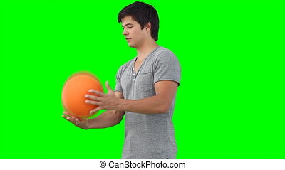 A man practises spinning a basketball on his finger against...