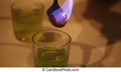 A man prepares a cocktail of absinthe. Sugar, moistened with...