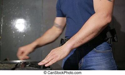 a man preparing to shoot a gun. puts the gun in the holster