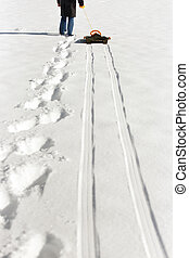 man pulling a sledge in the deep snow, footprints and tracks