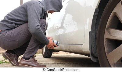 A man puts a homemade explosive device under the car....