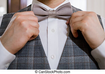 a man puts on a bow tie with his hands