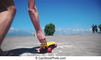 A man puts the penny board on the ground and standing on it
