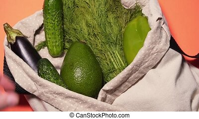 A man puts vegetables in a cotton bag on an isolated colored background. Cucumbers, tomatoes, avocados and other vegetables in a recycle cloth bag. Top view, static shot 4k