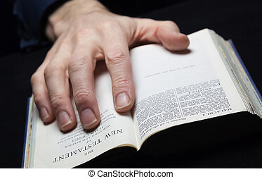 A man reading the Holy Bible with one hand.