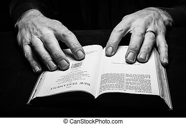 A man reading the Holy Bible with two hands.