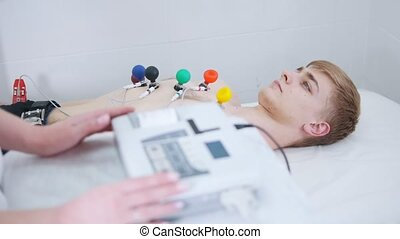 A man receiving a ECG procedure. A results tape coming out...