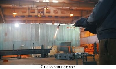 A man regulates the pressure in the welding machine. Middle...