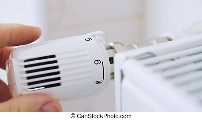 A man regulates the temperature in the house with a...