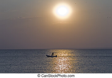 A man relaxing on a boat at Sunset