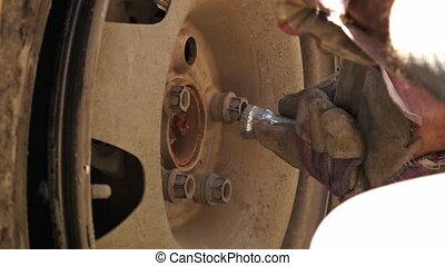 A man removing lug nuts using wheel wrench, Ladakh road - ...